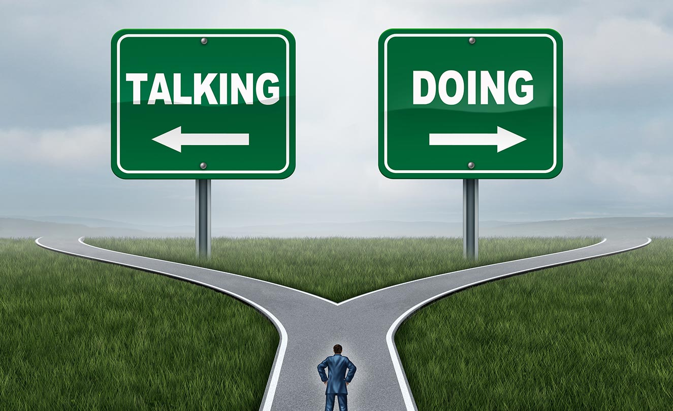 """2 Signs Reading """"Talking"""" and """"Doing"""""""