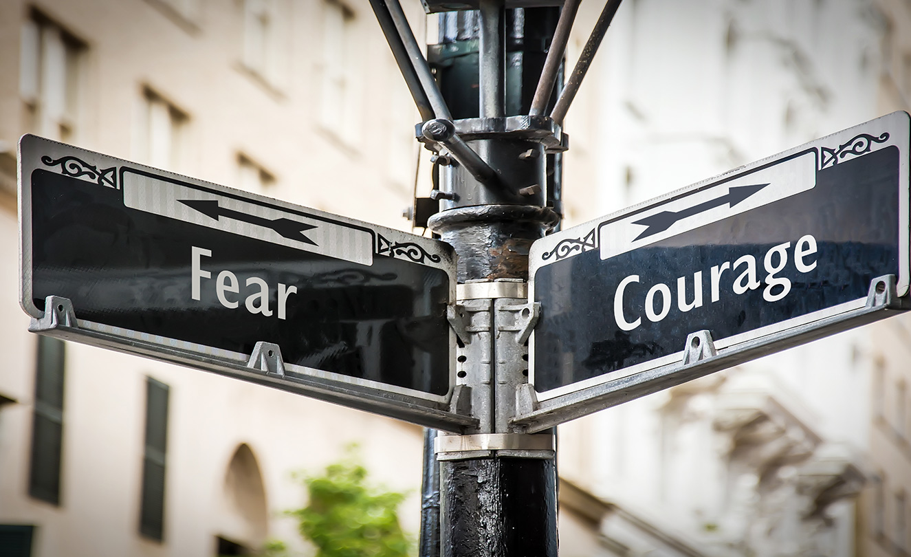 "Street signs reading ""Fear"" and ""Courage"" with arrows."