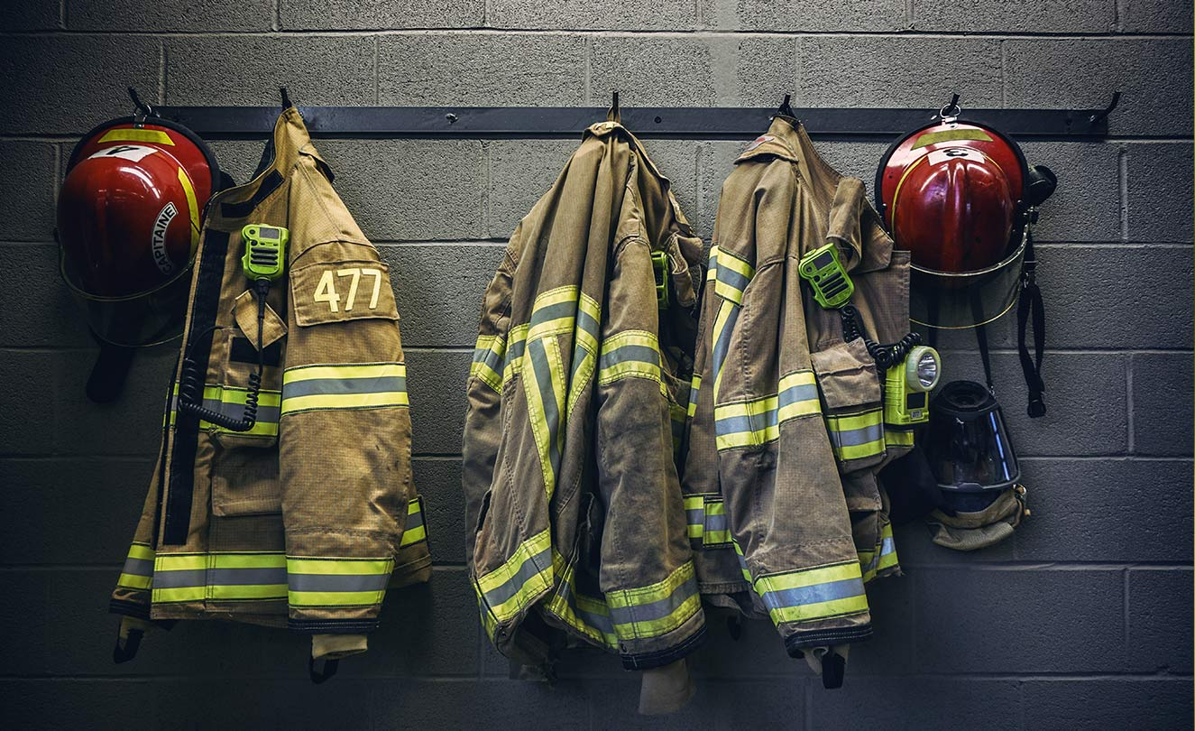 Firefighter suits hanging on wall. Not your momma's oral.