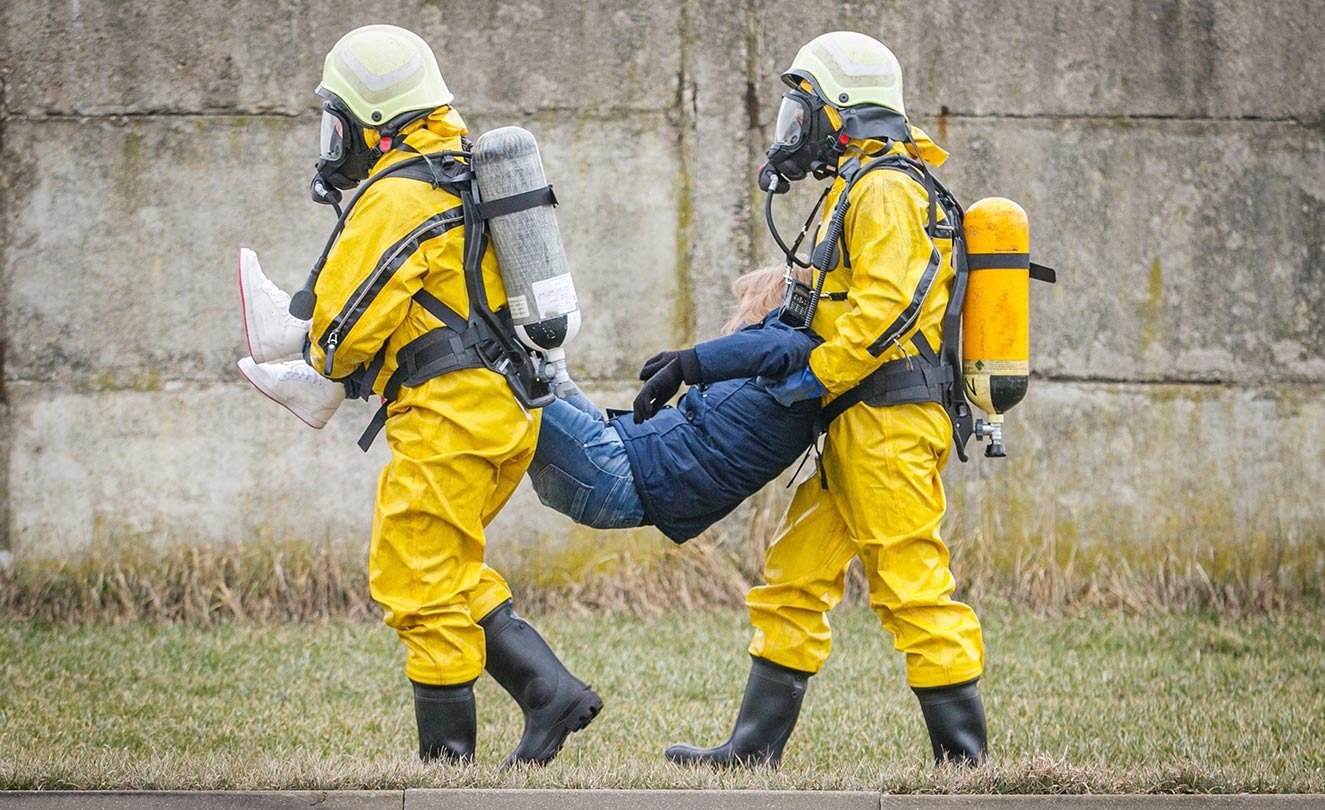 Two fireman practicing carrying a victim