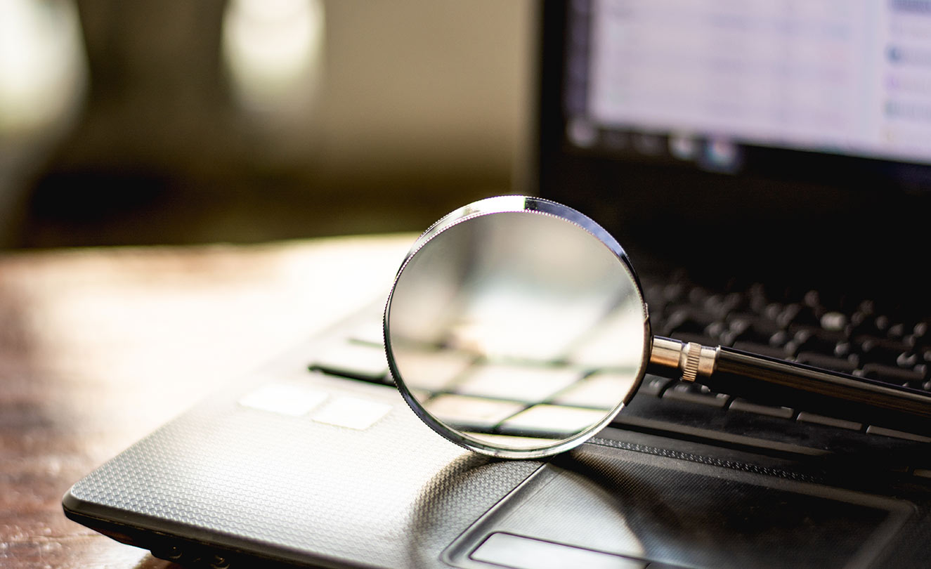Magnifying glass on a laptop computer. The background check.