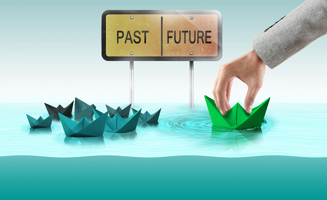 """Paper boats in water with sign that says """"Past"""" and """"Future""""."""