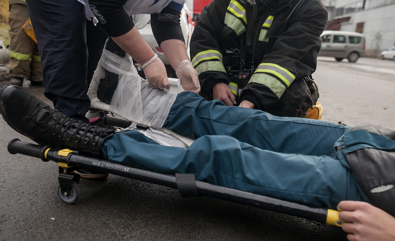 Man on stretcher being helped by firemen.