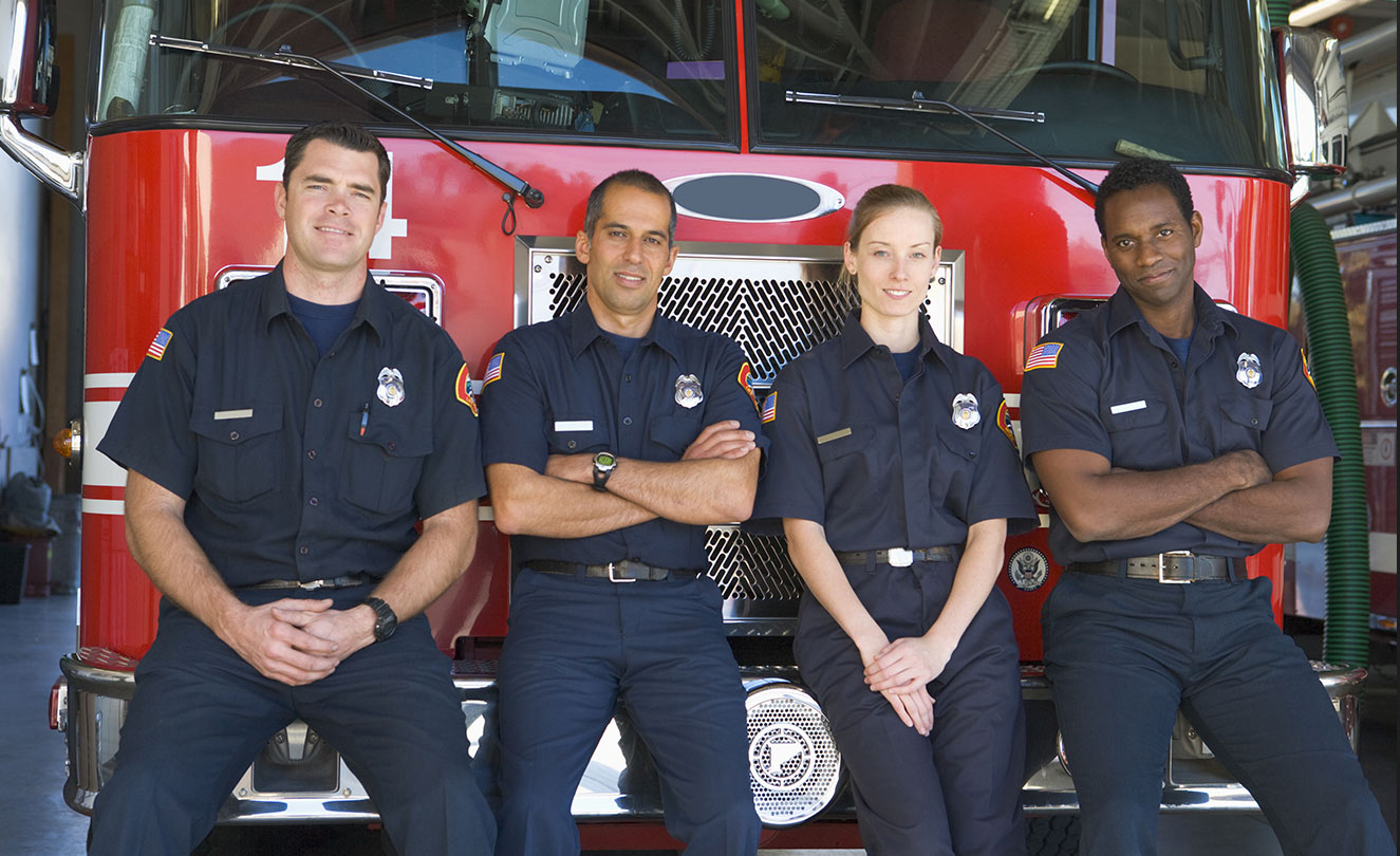 Four firefighters leaning against fire truck.